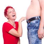 Frau sticht in dicken Bauch und lacht