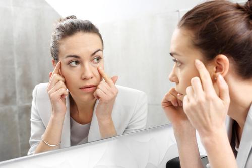 Odbicie w lustrze.Kobieta przeglda si w lustrze dostrzegajc pi